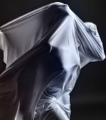 stock photo of struggle  - Art photo of a female silhouette breaking through the fabric - JPG