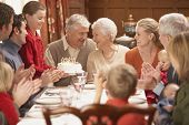 stock photo of family bonding  - Grandmother with birthday cake and family at dinner table - JPG