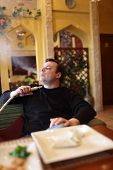 stock photo of shisha  - Man is smoking shisha in the restaurant - JPG