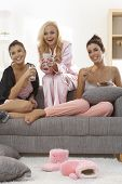 stock photo of pyjama  - Roommates sitting on sofa - JPG
