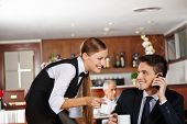 Waiter offering a pot of coffee to business man in hotel caf�?�?�?�©