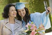 pic of grandmother  - Female graduate and grandmother taking picture with cellphone outside - JPG