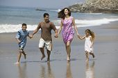 Happy family holding hands and running on the beach