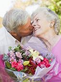foto of old couple  - Husband giving wife flowers outdoors kissing and smiling - JPG
