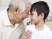 stock photo of 70-year-old  - grandpa telling a secret to grandson - JPG