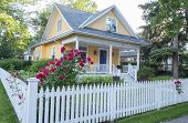 stock photo of house-plant  - Beautiful yellow house with white picket fence and pink rose bush - JPG