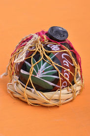 pic of mezcal  - Typical Mexican handicraft mezcal container made of black clay from Oaxaca Mexico on orange table - JPG