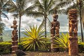 stock photo of tiki  - Three wooden Polynesian tiki carvings on Oahu Hawaii - JPG