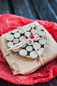 stock photo of heartfelt  - Gift decorated with wooden heart on red paper - JPG