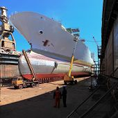 stock photo of shipbuilding  - A large cargo ship is being renovated in shipyard Gdansk Poland - JPG