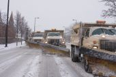 stock photo of spreader  - Four large city snow plows with salt spreaders  in tandem clearing the streets of snow during a winter snow storm in the Midwest - JPG