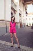 stock photo of jumpsuits  - Fashion and attractive woman dressed in a sexy sleeveless pink jumpsuit posing in full body length with long legs - JPG