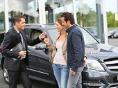foto of 35 to 40 year olds  - Salesman in car dealership giving keys to clients - JPG