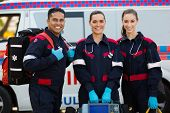 stock photo of jumpsuits  - happy paramedics carrying portable equipments in front of ambulance - JPG