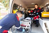 picture of stretcher  - team paramedics taking stretcher out of an ambulance - JPG