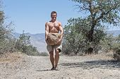 stock photo of struggle  - Muscular shirtless Caucasian man struggles to carry heavy boulder on dirt road in rural outdoor scene - JPG