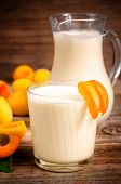 stock photo of apricot  - apricot milkshake with apricots slices on a dark wood background - JPG