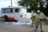 picture of decontamination  - firefighters in gas masks with foam extinguish a burning bus  - JPG