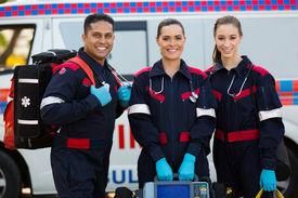 foto of ambulance  - happy paramedics carrying portable equipments in front of ambulance - JPG