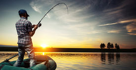 foto of jerks  - Mature man fishing from the boat on the pond at sunset - JPG