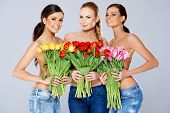 image of topless  - Three Sexy Topless Smiling Women in Jeans Covering their Chests with Fresh Beautiful Flowers While Looking at the Camera - JPG