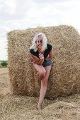 picture of shepherdess  - Beautiful young blonde woman outdoors near haystacks - JPG
