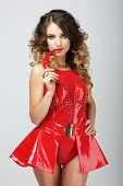 image of outfits  - Alluring Woman in Red Rubber Outfit biting Chili Pepper - JPG