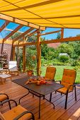 image of canopy roof  - View from a cozy winter garden in the large natural garden in summer - JPG