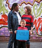 stock photo of homo  - a cute family holding a sign that read family  - JPG