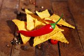 stock photo of nachos  - Tasty nachos and chili pepper on wooden background - JPG