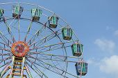 picture of ferris-wheel  - A colorful Ferris wheel at theme park against a blue sky - JPG