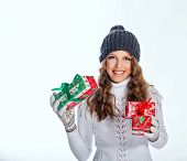 picture of knitted cap  - Cute teen girl in a knitted cap and sweater holds in her hands Christmas gifts - JPG