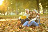 stock photo of grandparent child  - Grandparents and grandson together in autumn park - JPG