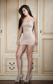 stock photo of tight dress  - Charming young brunette woman in tight fit short nude dress leaning against wooden wall - JPG