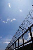 stock photo of razor  - barbed wire fence razor blur sky clouds - JPG