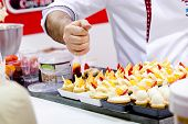 stock photo of whipping  - chef with cooking bag decorating cupcakes with whipped cream - JPG
