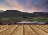 stock photo of cloud formation  - Stunning sunrise mountain landscape with vibrant colors and beautiful cloud formations with wooden planks floor - JPG