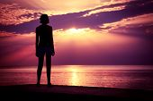 stock photo of breathtaking  - Silhouette of Young Woman Watching Sea Sunset - JPG