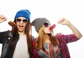 stock photo of swag  -  portrait of two young pretty hipster girls wearing  hats and sunglasses holding candys - JPG