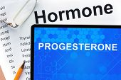 image of hormone  - Papers with hormones list and tablet  with word progesterone - JPG