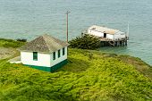 foto of bluff  - Small house on a bluff with a boathouse on a pier - JPG