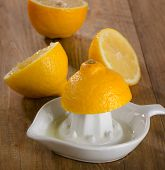 stock photo of juicer  - Lemons and juicer on a wooden background  - JPG