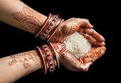 stock photo of pooja  - Woman hands with henna holding rice isolated on black background with clipping path - JPG