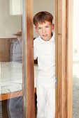 stock photo of peeking  - Surprised boy peeks from behind door indoor - JPG