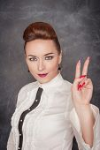 picture of cynicism  - Beautiful fashion woman showing victory sign on the blackboard background - JPG