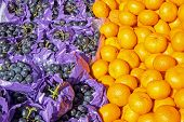 picture of clementine-orange  - Clementines and grapes for sale at a market - JPG