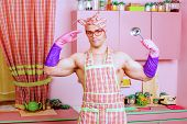 stock photo of ladle  - Attractive muscular man in an apron posing with a ladle with expression - JPG