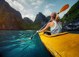 stock photo of kayak  - Woman exploring calm tropical bay with limestone mountains by kayak - JPG