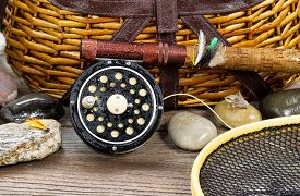 foto of fly rod  - Close up of a wet antique fly fishing reel rod landing net artificial flies and rocks in front of creel with rustic wood underneath - JPG
