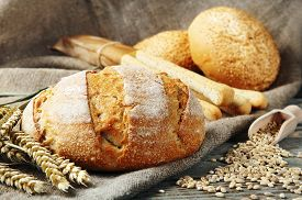 image of seed  - freshly baked homemade bread on a wooden table. Next to the bread two whole eggs scattered the seeds of wheat two buns with sesame seeds and bread sticks with poppy seeds. rustic style. closeup